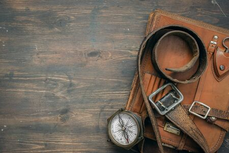 Compass and old leather bag on the adventurer table flat lay background with copy space. Фото со стока