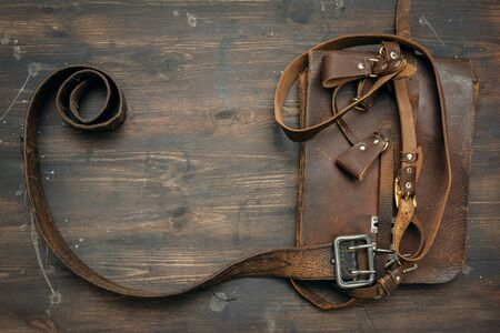 Old leather brown bag and belt on wooden background with copy space.
