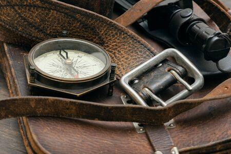 Old travel equipment and adventurer accessories on the wooden table flat lay background. Фото со стока