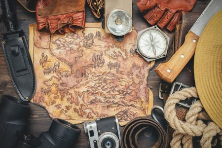 Old treasure map and adventurer equipment on the old table background.