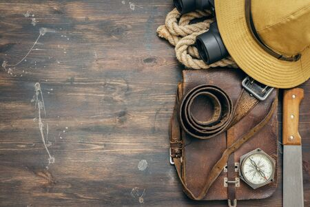 Old travel equipment on the wooden table flat lay background.