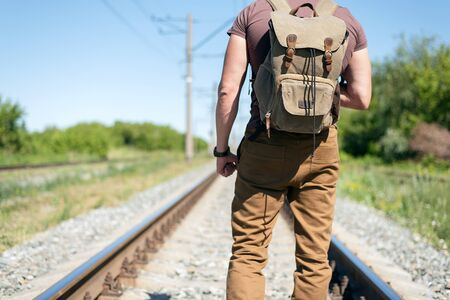 Traveler with a backpack is walking on empty railway road.