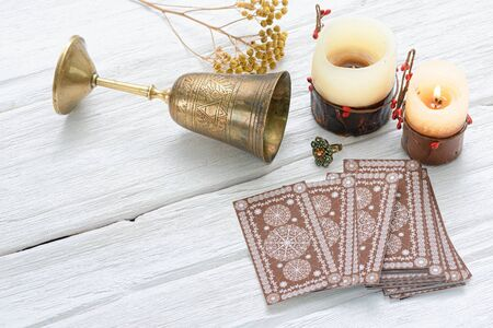 Tarot cards and golden goblet on white table of fortune teller. Divination. Future reading concept.