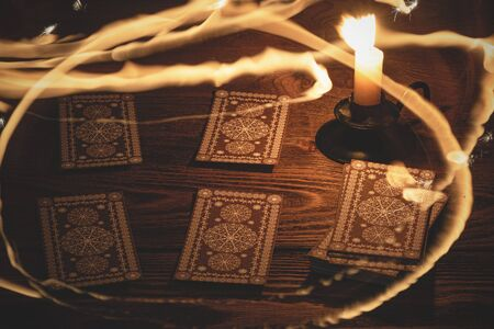 Tarot cards and magic flame around the table. 写真素材