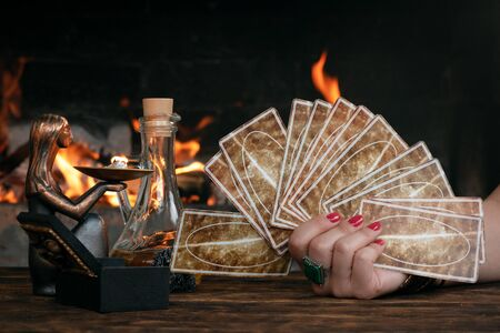 Tarot cards on fortune teller table on a burning fire background. Futune reading concept. Divination.
