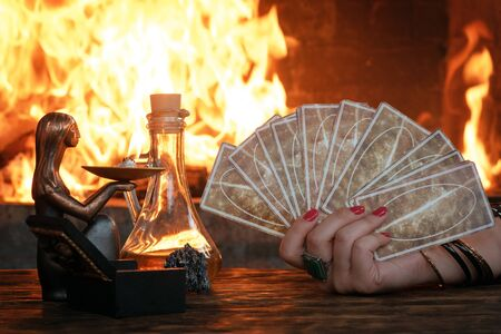 Tarot cards on fortune teller table on a burning fire background. Futune reading concept. Divination. Reklamní fotografie
