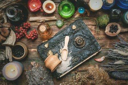Book of magic and other magical accessories on wooden table background. Witchcraft. Witch doctor.