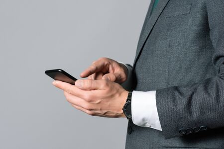 Businessman is writing sms on his mobile phone on gray background.