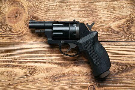 Pneumatic handgun on brown wooden board background.