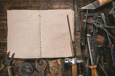Carpentry or construction tips book with copy space and old tools on wooden workbench background.
