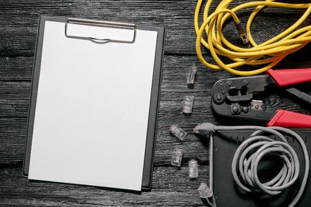 Computer network laying concept. Blank paper page, crimper tool, utp cable, net switch and conncectors on black wooden table background.