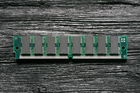 Old computer ram memory module on black wooden background.