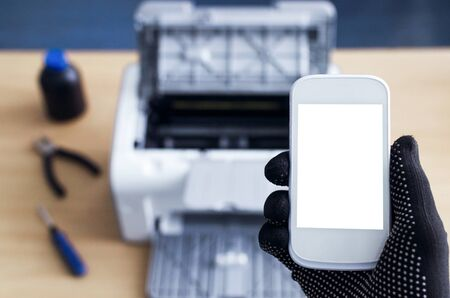Call to printer repair service mockup. Blank screen mobile phone and broken printer on the table. Stock Photo