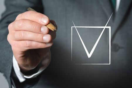 Tick in a checkbox and businessman hand with a ball pen close up background. Banco de Imagens