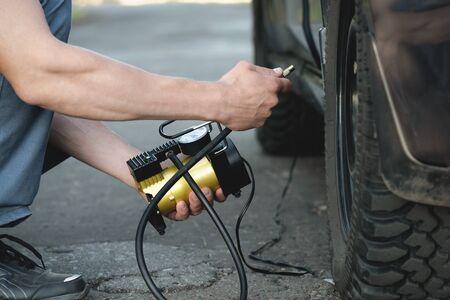 Driver is pumping the car wheel with a car pump. 版權商用圖片