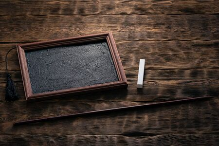 Blackboard frame, school pointer and piece of chalk on a brown wooden background. Education concept.