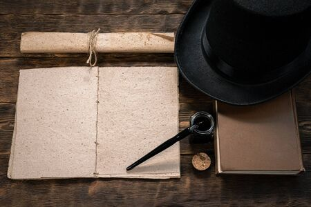 Open blank page book, old scroll, quill pen, bowler hat and burning candle on a writer wooden table background. Banque d'images