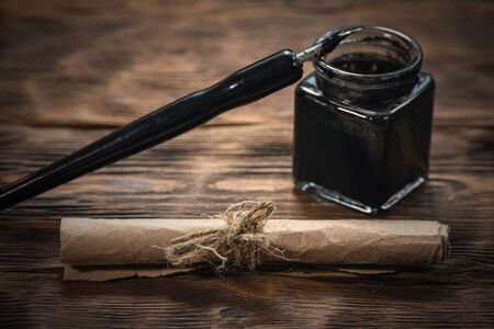 Old parchment letter wrapped by rope, quill pen with inkwell on brown wooden desk background.