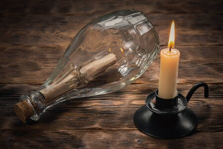 Pirate letter parchment in a glass bottle and burning candle on brown wooden table background.