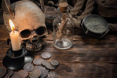 Pirate letter parchment in a bottle, human skull, old coins, compass and burning candle on a brown wooden table background.