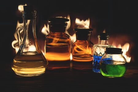 Magic potions bottle in the light of fire background.