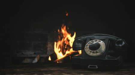Black old phone on a table on a burning fire in fireplace background. Hotline concept.
