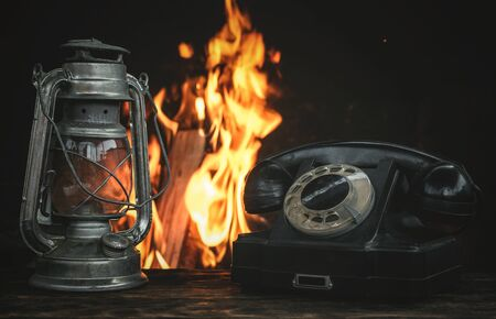 Black old phone and kerosene lamp on a table on a burning fire in fireplace background.