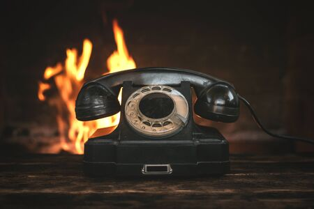Black old phone on a table on a burning fire in fireplace background. Hotline concept. Banque d'images