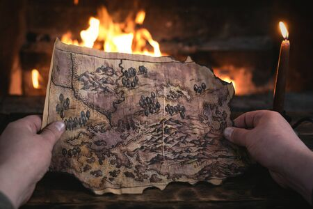 Adventurer man is holding in hands a treasure map over a burning fire background. Treasure hunt concept. Banque d'images
