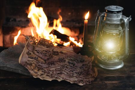 Pirate treasure map and kerosene lamp over a burning fire background. Treasure hunt concept. Banque d'images