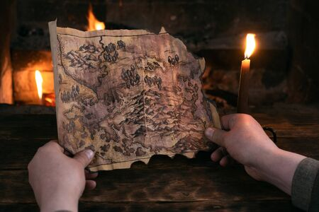 Adventurer is holding in hands a treasure map over a burning fire background. Treasure hunt concept.