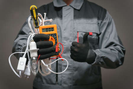 Electrician worker is holding in hands a multimeter with wires and is showing a thumbs up gesture close up.