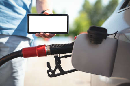 Mobile phone in the driver hand on car fuel nozzle in the car gas tank background.