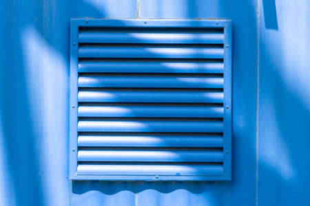 Ventilation grid on blue wall background.