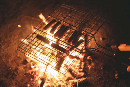 Grill with sausages on the coals of campfire.