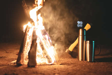 Ax,   steel cup on the ground near the burning bonfire at night camping background. 版權商用圖片 - 151946416
