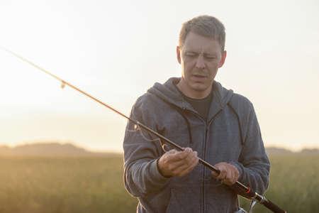 Fisher with fishing rod outdoors. 版權商用圖片 - 151860245