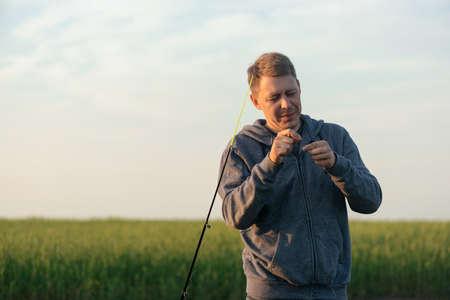 Fisher with fishing rod outdoors. 版權商用圖片 - 151860240