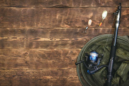Fishing flat lay background with a copy space. Fishing gear on a wooden table.