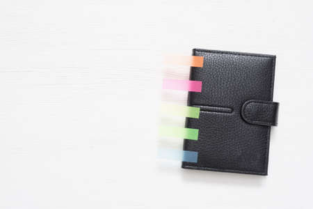 Black leather wallet with colorful stickers on the white table background with copy space.