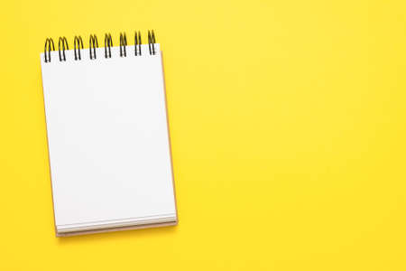 Blank page of notepad on the yellow flat lay background with copy space.