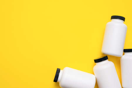 White plastic jars on the yellow flat lay background.