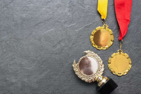 Golden medals award trophy on the stone table surface flat lay bakcground with copy space.