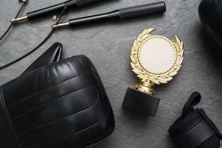 Boxing gloves, jumping rope and golden award trophy medal on the gray flat lay background.