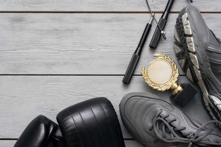 Boxing gloves, sneakers, jumping rope and golden award trophy on the wooden floor flat lay background with copy space.