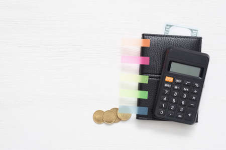 Wallet with money and calculator on the white flat lay table background with copy space.