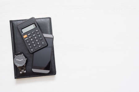 Black leather ledger book, calculator, mobile phone and wrist watch on white flat lay background with copy space. 版權商用圖片 - 152886829