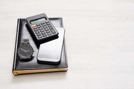 Black leather ledger book, calculator, mobile phone and wrist watch on white flat lay background with copy space.