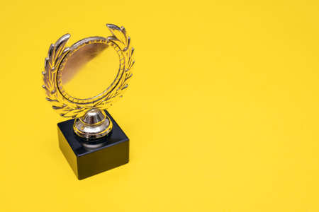 Golden medal award trophy on the yellow background with copy space.
