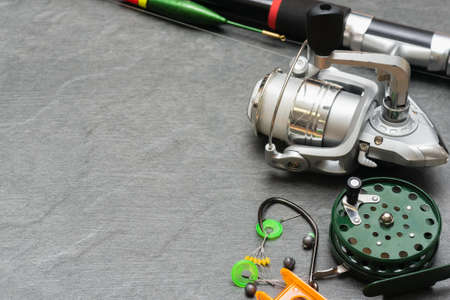 Fishing rod with reel on gray background with copy space. Fishing accessories on the table. 版權商用圖片